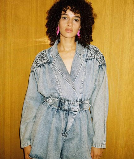 Blue denim jumpsuit featuring gathered padded shoulder, wrap front style and self fabric covered button. Photo 1